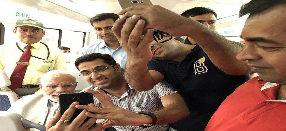 PM Modi takes Airport Metro ride to Dwarka event; passengers take selfies with him (Photo- Twitter/@PMOIndia)