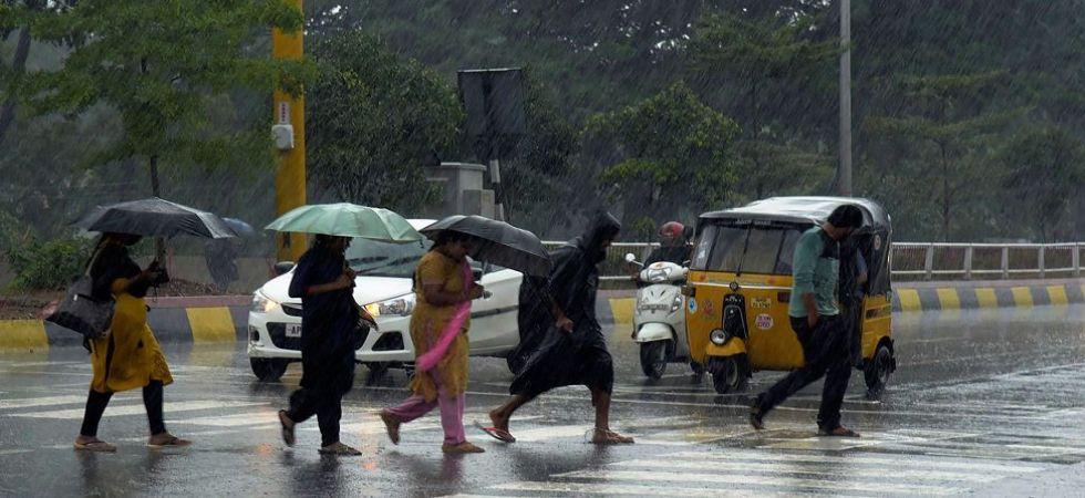 People walk across a road during heavy rainfall as Cyclone wreaked havoc through coastal Andhra Pradesh (Photo Source: PTI)