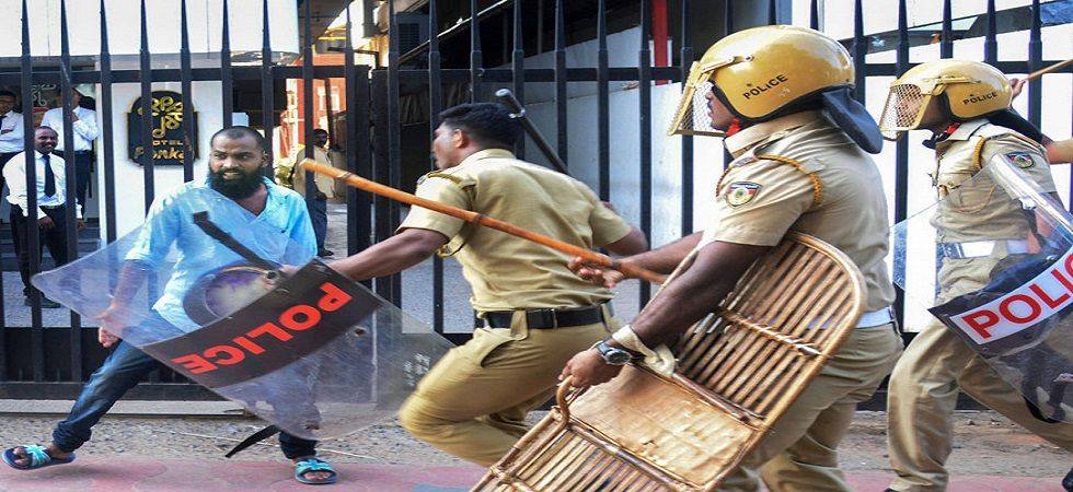 Policemen chase away a man during a protest against the entry of two women to the Sabarimala temple, in Thiruvananthapuram. (Photo: PTI)