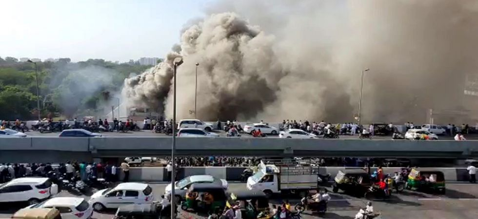 Smoke billows from the Taxshila Complex as vehicles ply on the road in Surat (Photo Source: PTI)