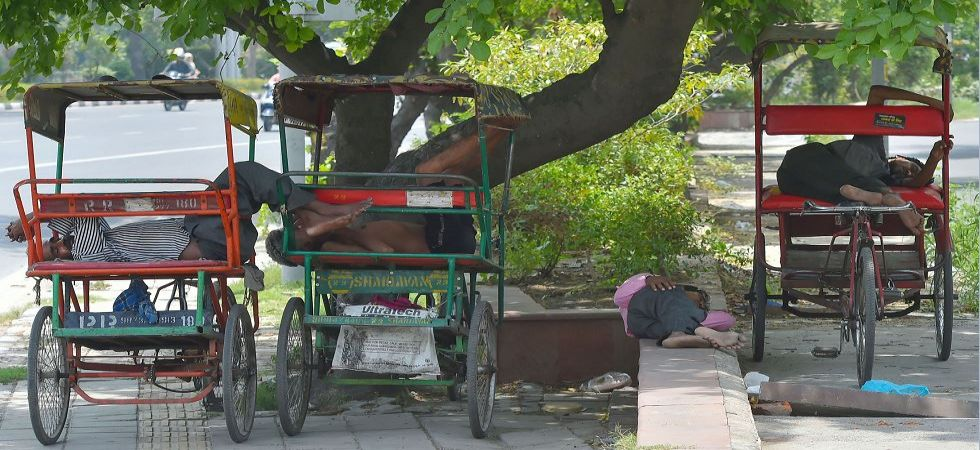 Rickshaw-pullers sleep in the shade of a tree along a road, on a hot summer day in New Delhi (Photo Source: PTI)