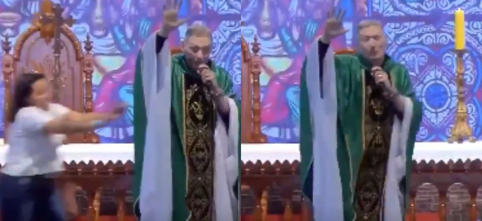 Woman pushes priest off stage. (Image: Twitter)